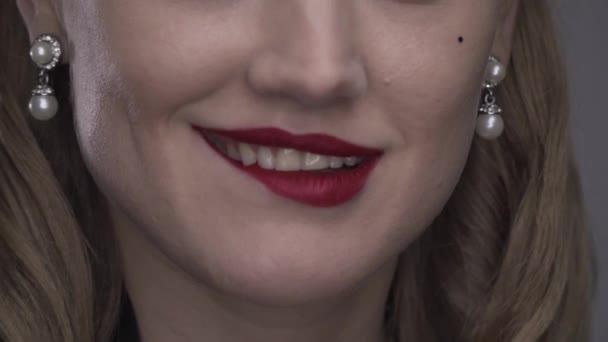 Junge Frau mit rotem Lippenstift beißt ihre Lippe und lächelt, Nahaufnahme, 4k
