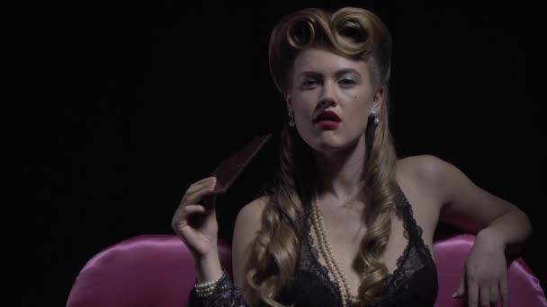 Pin up Frau aus den 50er Jahren beißt einen großen Schokoriegel und leckt ihre Lippen