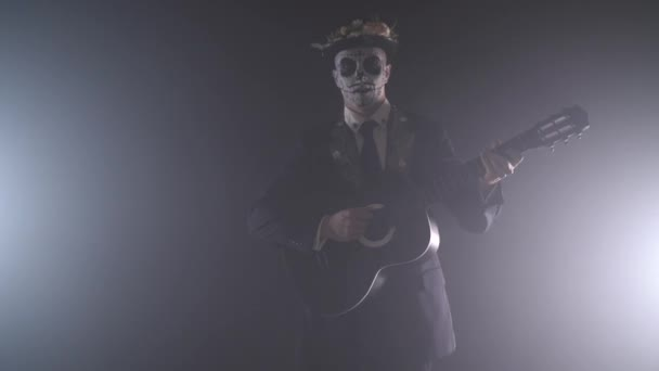 Mann mit der Farbe eines Schädels auf seinem Gesicht spielt gitarre in einem rauchigen Raum