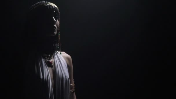 Cleopatra wearing jewelry with colorful gems is standing in dramatic lighting