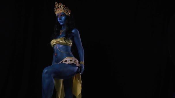 Una dea indiana Kali che indossa abiti doro è in piedi su sfondo nero