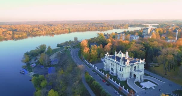 Aerial photography. Bright yellow autumn forest. Blue River. Reflections of trees in the water. Embankment and old noble house.