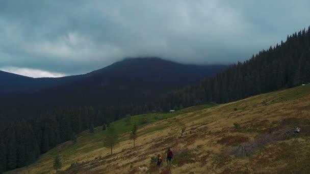 Letecký pohled na krásné Karpaty krajina při západu slunce s nízkými mraky a pěší backpackers