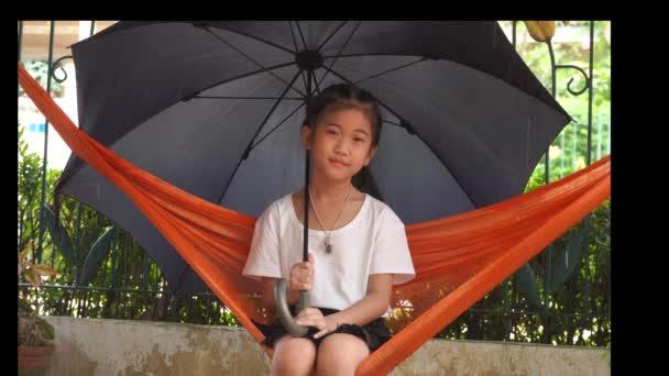 Kinder unter dem Regenschirm auf der Hängematte, wenn es regnet.