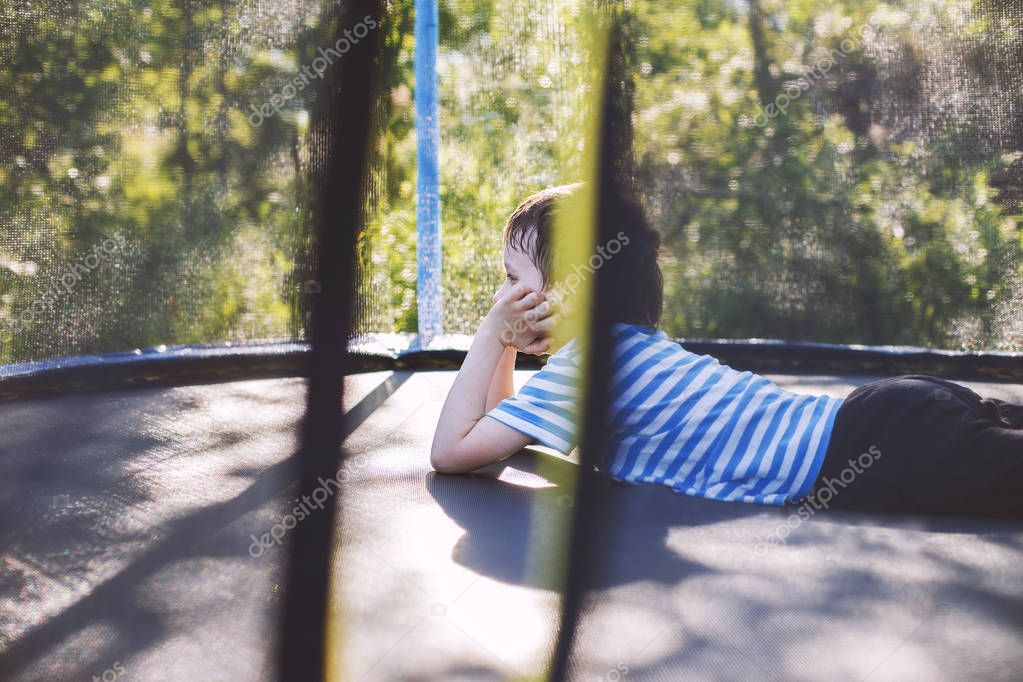 boy on  the trampoline. the child lies on a trampoline and rests