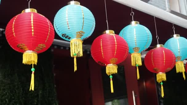 Chinese lanterns sway in the wind in the afternoon. Oriental paper lights of red and blue colors are swaying with the wind on the roof of a building by day on the street