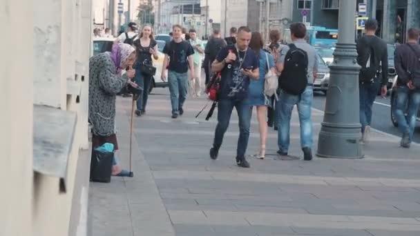 Moskau, Russland - 6. September 2018: Eine ältere Frau bittet Passanten auf der Straße um Almosen. Der Rentner steht gebückt mit einem Stockkreuz da und bittet die Leute um Geld. Einsamkeit