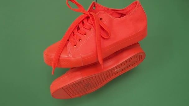 Dvojice červených teniskách visí na zeleném pozadí. Oranžové boty viset na laně