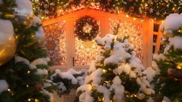 Tannenkranz hängt an der Tür eines fabelhaften Hauses mit Ornamenten an den Fenstern und Weihnachtsgirlanden, die oben mit Weihnachtskugeln und Lichtern geschmückt sind. - schöner Hintergrund der Saison