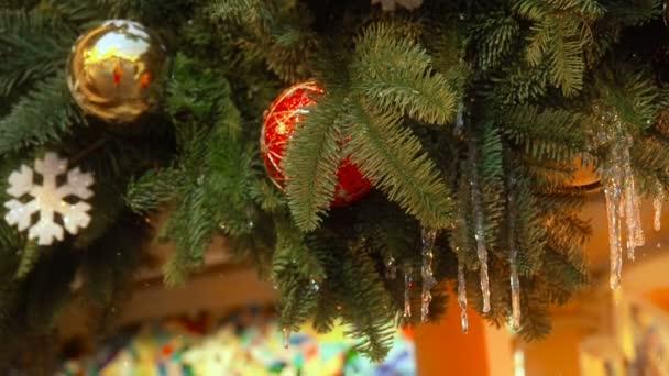 Červené a žluté kuličky vánočního stromového zdobení s tavením a zvolna padající sněhovou výzdobou zavěšené na sezoně. Vánoční dekorace, hračky pro vánoční stromku-nový rok dovolená