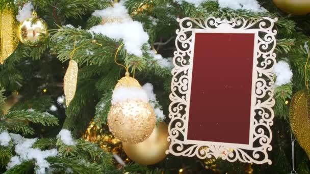 Göndör faragott képkeret lógó fenyő fa hintett a hó. Beszúrt faragott piros Backgrounf into a fehér keret. Üres fotókeret üres mintadarab sablon