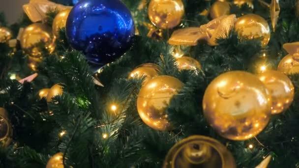 Közelről a karácsonyfa fények csillogó éjjel. Újévi fenyőfa dekorációkkal és megvilágítással. Xmas fa dekoráció háttér. Sok nagy arany golyó fenyőfa Szilveszter és a karácsony