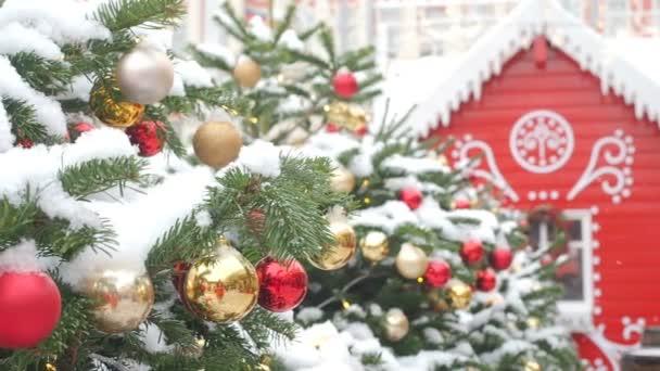 Zlaté a červené koule visící na vánočním stromku pokryté sněhem a červeným perníku. Krásná dekorovaná ulice pro Vánoce a nové roky dovolené.