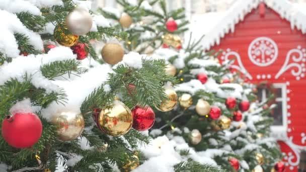 Zlaté a červené koule visící na vánočním stromku pokryté sněhem a červeným perníku. Krásná dekorovaná ulice pro Vánoce a nové roky dovolené