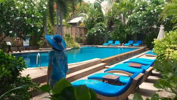 Hezká dáma v modrých plavkách, klobouku a slunečních brýlích, procházející se po bazénu s průzračnou vodou za slunečného dne. Luxusní letovisko se topí v zeleni. Plavecký průzkum s modrými lehátky ve stínu