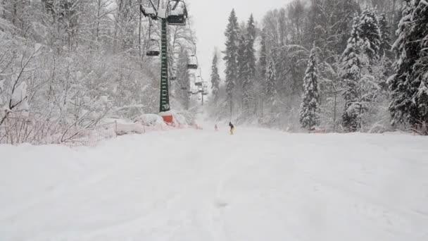 Dolní pohled na dvousedačkovou lanovku na sjezdovce v zimním zasněženém lese. Sedačková lanovka stoupá nad sjezdovku v malém lyžařském středisku Stepanovo během sněžení. Lidé jezdí na lyžích a snowboardu