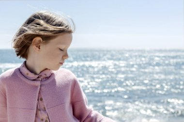 Little cute girl (7 years old) is standing against the sea in a