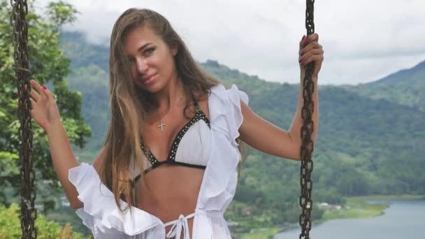 sexy Mode Frau schwingt auf Schaukel bali auf Vulkan oben