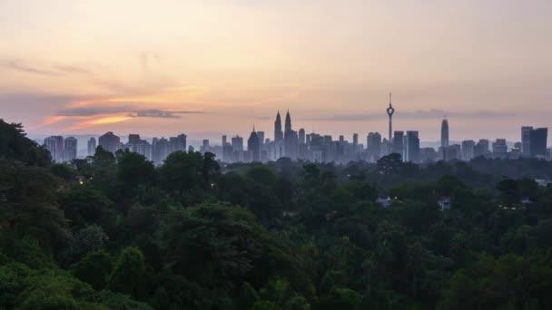 4k time lapse of sunrise from the horizon of Kuala Lumpur city skyline. Pan left