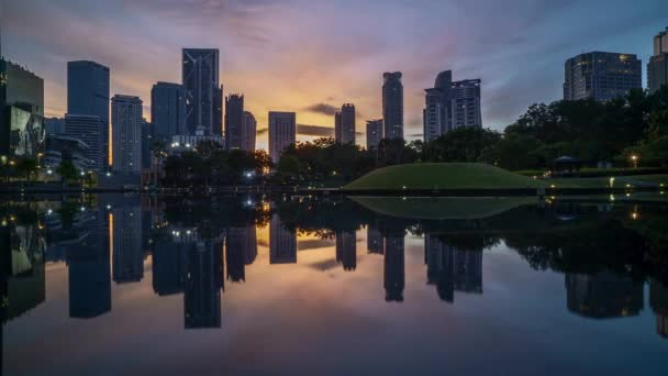 4k time lapse of sunrise at Kuala Lumpur city skyline with reflection on water.