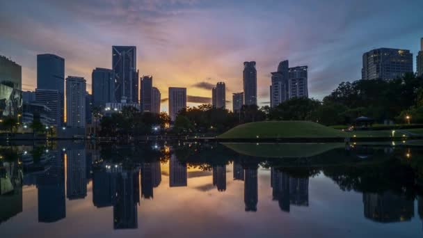4k time lapse of sunrise at Kuala Lumpur city skyline with reflection on water. Tilt down