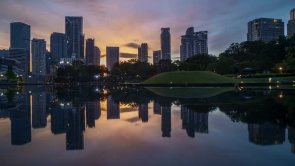 4k time lapse of sunrise at Kuala Lumpur city skyline with reflection on water. Pan left