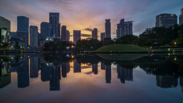 4k time lapse of sunrise at Kuala Lumpur city skyline with reflection on water. Zoom in