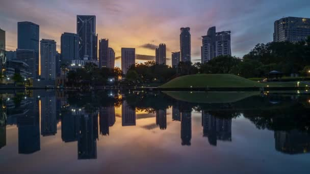 4k time lapse of sunrise at Kuala Lumpur city skyline with reflection on water. Zoom out