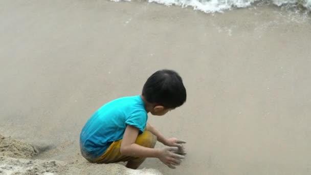 Zeitlupenaufnahmen eines asiatischen (melayu) malaysischen Jungen, der an einem Strand Sand spielt.