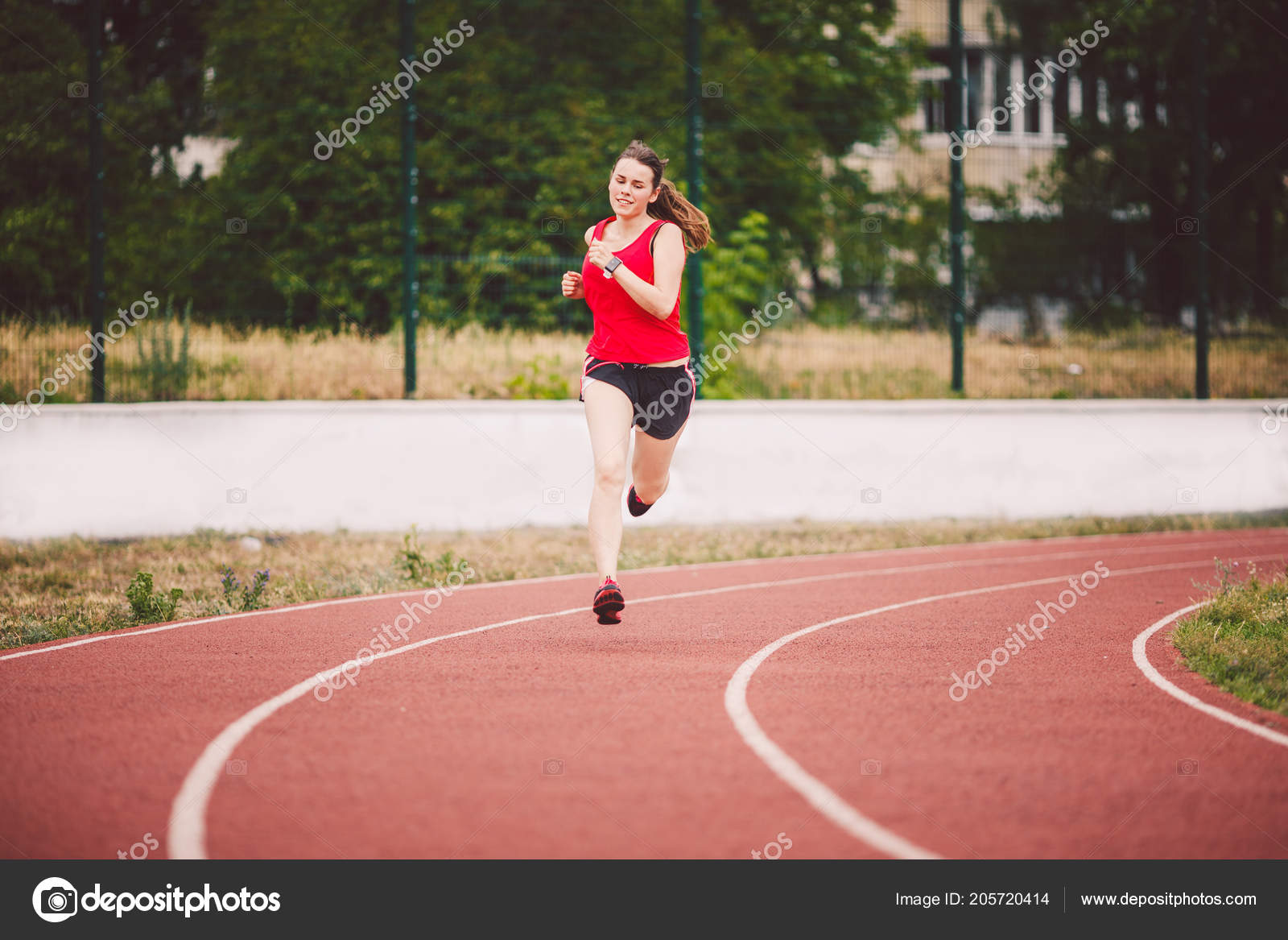 f7d2139c9b Beautiful young athlete Caucasian woman with big breasts in red T-shirt and short  shorts running jog