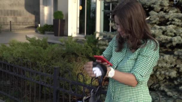 Mladý student Kavkazský žena používá ruční držení telefonu dotyková obrazovka. Žena stojí poblíž pronájem městské kolo za slunečného počasí na chodníku v helmě a košili. Odpočívadlem přestávka