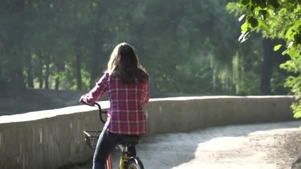 Předmět kolo ekologické dopravy. Mladá běloška jízda na polní cestě v parku nedaleko jezera pronájem oranžové kolo na podzim za slunečného počasí