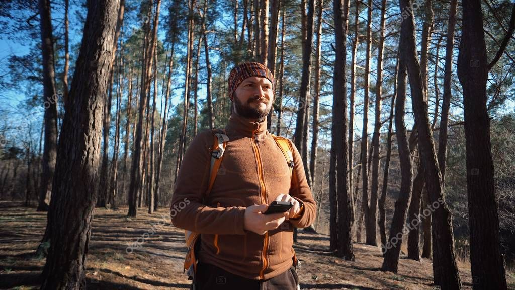 theme tourism and technology. Young caucasian man with beard and backpack. Hiking tourist in pine forest uses technology, hand holding mobile phone to touch the screen. Gps application orientation