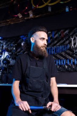 Portrait of small business owner of young man with beard. Guy bicycle mechanic workshop worker sitting with tool in his hand in a working black clothes in an apron in the background of a bicycle shop