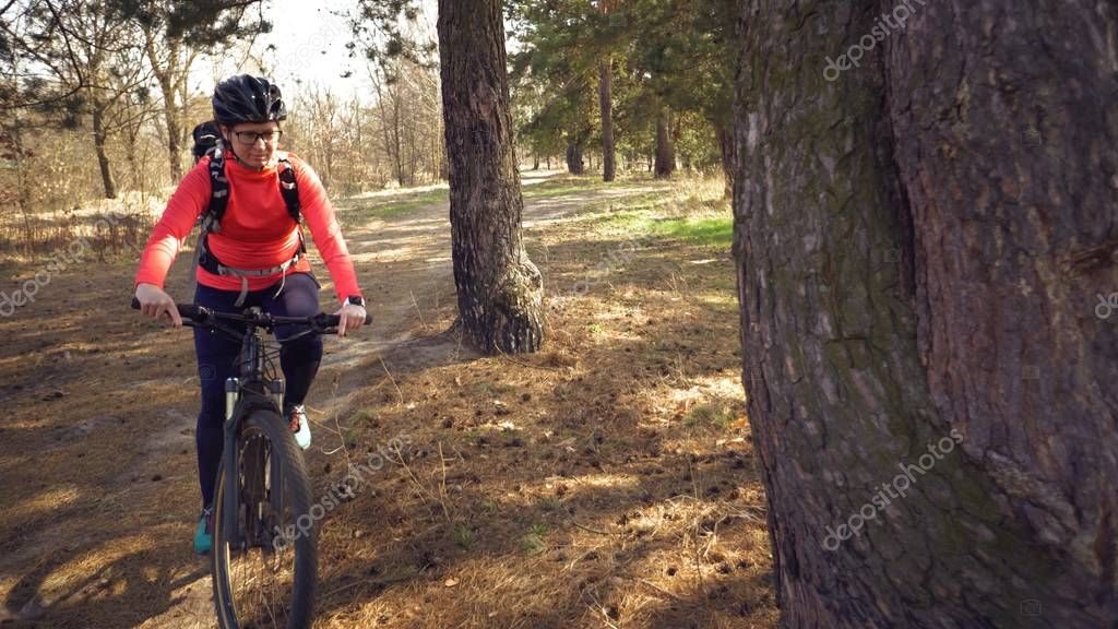Cyclist. Caucasian sport woman rides along the track in the forest on a spring sunny day. Riding a sportsman girl on a mountain bike on a rural trail in nature. Outdoor sports
