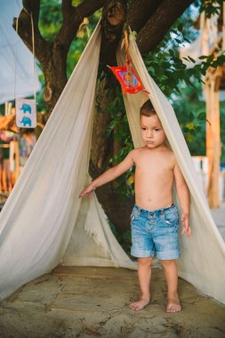 theme summer vacation, little boy, Caucasian child playing in wooded area in park on playground in yard. kid in Tipi wigwam tent in summer. Explore and play in nature on summer time