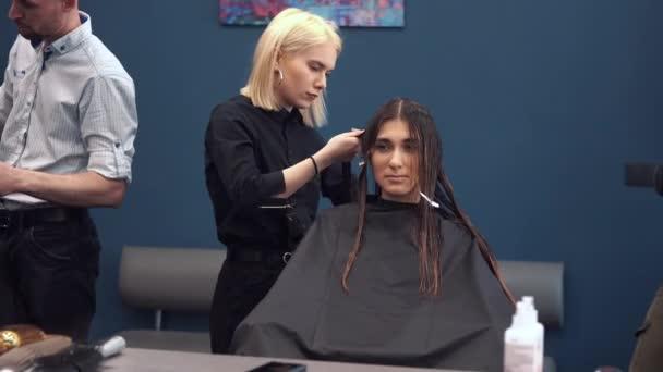 szép nő hullámzó nedves hajat. stylist fogmosás nő haját a szalonban. Fodrászat kiszolgáló ügyfél. Szakmai fiatal fodrász dolgozó fésű. hajápoló koncepció. Vizes Hajfésítés fodrászat