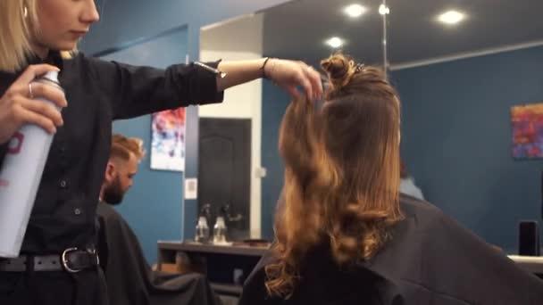 fodrászat segítségével hajlakk a vendég haj a szalonban. Hajformázó. Stylist Making frizurát a Barbershop. Fodrászat, hogy a haj stílusa az ügyfél a hajlakk a szalonban