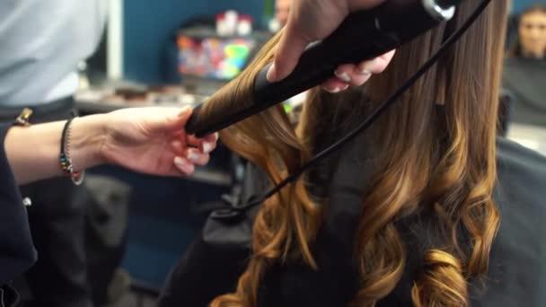 szépség, frizura koncepció, boldog fiatal nő és fodrász hajvasaló, hogy frizura a fodrászat. Nő, akinek stilizált a frizurája. Smoothes haj curling. Stylist eszköz modellezéshez