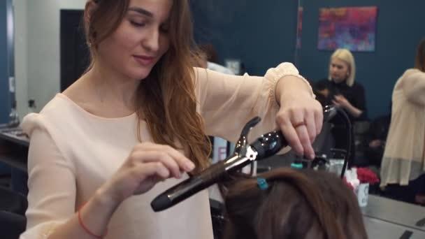 krása, účes koncept, šťastná mladá žena a kadeřník s vlasy železo dělat účes v kadeřnictví. Žena s účesem stylizované kadeřnice. Uhlazuje kadeřnictví. Stylista používající nástroj pro modelování