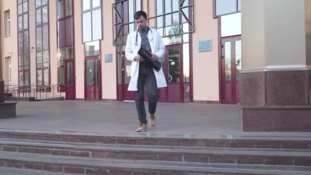 Doktor v laboratorním kabátě, stetoskop analyzující rentgen, stojí poblíž hlavního vchodu do nemocnice. Mladý zdravotnický pracovník, internetový radiolog vyšetření mri x-ray plic během epidemie COVID 19