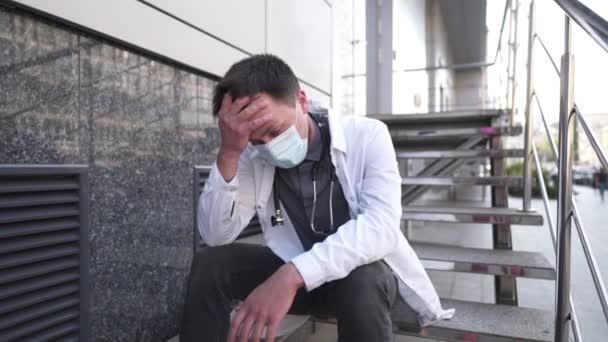 Besorgter und müder Arzt sitzt auf der Treppe vor dem Krankenhaus. Erschöpfter Arzt in weißem Laborkittel und medizinischer Schutzmaske sitzt im Treppenhaus der Klinik. Stress im Gesundheitswesen während der COVID-19