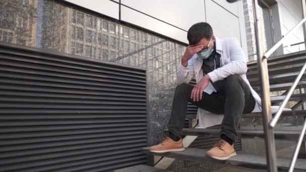 Kaukasischer junger Arzt setzt sich auf die Treppe in der Nähe des Klinikgebäudes, müde und unglücklich reibt er sich Nase und Augen, fühlt sich müde und hat Kopfschmerzen. Konzept für Stress und Frustration im Gesundheitswesen