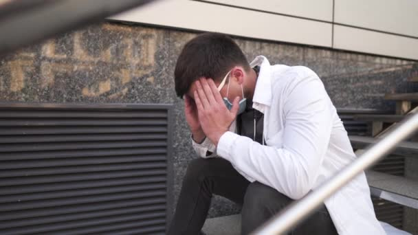 Ernsthafter Arzt ruht nach langer Schicht im Krankenhaus auf der Treppe. Müder Arzt in Maske, weißer Uniform und Stethoskop, während er auf der Treppe vor der Klinik sitzt, Kopfschmerzen und sich die Augen reibt