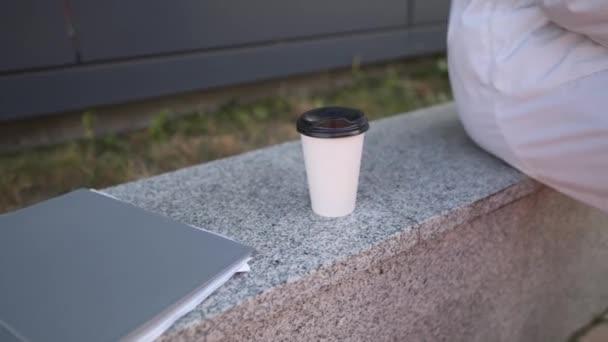 Der umtriebige Arzt hat genug zu tun, Kaffeepause nach harter Schicht im Krankenhaus. Übermüdeter Arzt wirft Krankenakte mit Dokumenten und trinkt Heißgetränk Kaffee to go aus Pappbecher. Überstunden