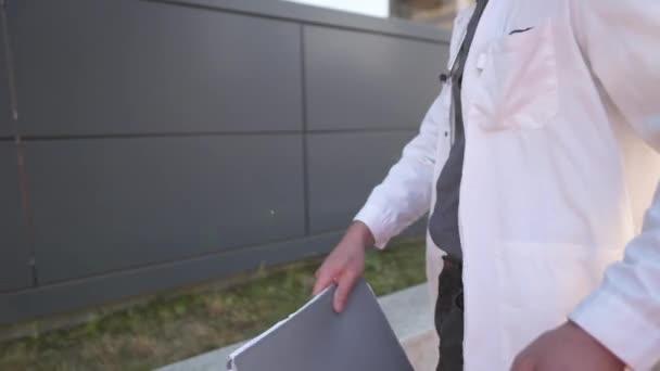 Ein hübscher kaukasischer Arzt tauscht medizinische Dokumente gegen eine Tasse Kaffee im Einwegbecher aus. Müdes medizinisches Personal ging zur Pause auf den Hof des Krankenhauses, wirft Krankengeschichte und trinkt Kaffee to go
