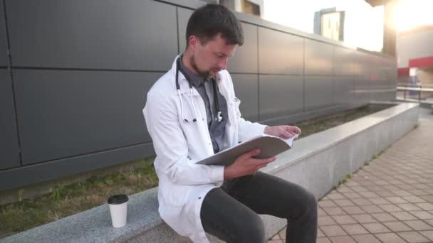 Müder überlasteter Arzt liest ärztlichen Bericht. Gestresster Arzt. Erschöpfter Arzt ruht sich aus, nachdem er Krankenakten gelesen hat. Medizinkonzept. Müder Arzt im weißen Kittel hält Ordner mit Dokument in der Hand