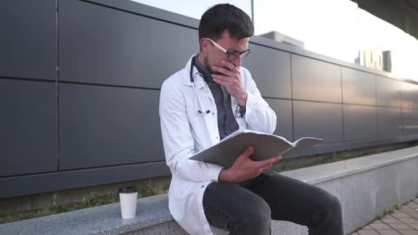 Junger Arzt arbeitet während einer Kaffeepause im Hinterhofkrankenhaus mit medizinischen Dokumenten. Müder Arzt im weißen Laborkittel untersucht Anamnese, Krankengeschichte und trinkt Heißgetränk außerhalb der Klinik