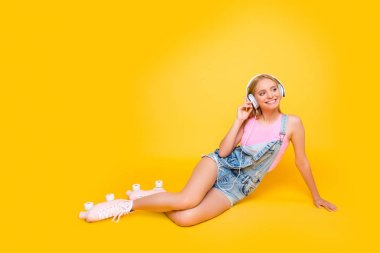 Portrait of pretty positive girl in roller skates listening favorite music using headset, looking away, isolated on yellow background, delight daydream concept
