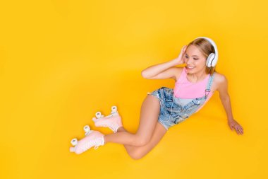 Portrait of pleased girl using headphones listening favorite music wearing roller skates having pleasure enjoyment delight free time daydream isolated on yellow background, looking away